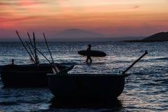 Silhouet van een mens met een surfplank in het overzees bij zonsondergang Royalty-vrije Stock Afbeeldingen