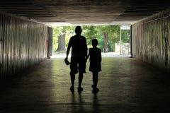 Silhouet van een mens met een kind in een donkere tunnel stock foto's