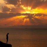 Silhouet van een mens op een klip Stock Afbeelding