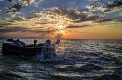 Silhouet van een mens op een opblaasbare matras die in het water van Kaspische Overzees in zonsondergangtijd zwemmen Zomer in Aze Stock Afbeeldingen