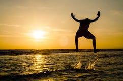 Silhouet van een mens in een springende positie in het overzees bij sunse royalty-vrije stock afbeeldingen