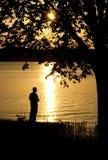 Silhouet van een mens visserij Stock Afbeeldingen