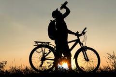 Silhouet van een mensen drinkwater met fiets bij zonsondergang stock foto's
