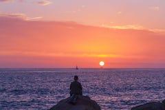 Silhouet van een mensenzitting op de rotsen die van de zonsondergang voor de oceaan genieten, Royalty-vrije Stock Foto's
