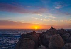 Silhouet van een mensenzitting op de rotsen die van de zonsondergang voor de oceaan genieten, Royalty-vrije Stock Foto