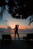Silhouet van een mooi slank meisje op van de zonsondergang achtergrond en zon lanterfanters op de oceaankust De horizon van het v Stock Afbeelding