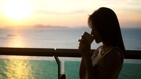 Silhouet van een mooie Aziatische vrouw die een kop van koffie met warme middagzonsondergang drinken bij de oceaan op de achtergr stock fotografie