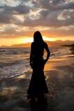 Silhouet van een mooie vrouw op de achtergrond van het overzees bij zonsondergang Stock Foto's