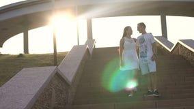 Silhouet van een paar dat de treden lopend in het park bij zonsondergang daalt stock videobeelden
