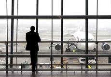 Silhouet van een reiziger die op een vliegtuig wachten stock foto