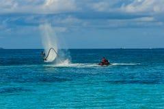 Silhouet van een ruiter van de vliegraad op zee De professionele ruiter doet trucs in de blauwe lagune Tropisch water-sport mater stock afbeelding
