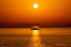 Silhouet van een schip die in de bezinning van de Zon in het Ionische Overzees, Sarande, Albanië overgaan stock afbeelding