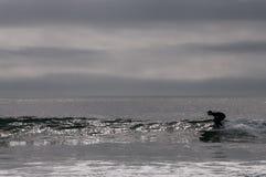 Silhouet van een surfer die een golf vangen stock foto's