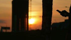 Silhouet van een tablet en handen bij zonsondergang De zononderbrekingen door de bouw van een wolkenkrabber stock video