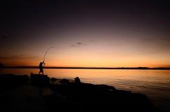 Silhouet van een visser stock foto's