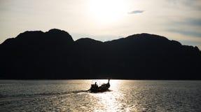 Silhouet van een visser en een boot Stock Fotografie
