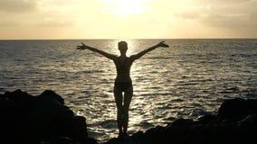 Silhouet van een vrouw bij zonsondergang die golven waarnemen en wapens in de lucht opheffen Cinematic Langzame Motie stock video