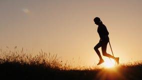 Silhouet van een vrouw die - door de kabel bij zonsondergang springen stock afbeeldingen