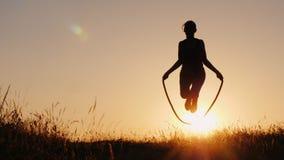 Silhouet van een vrouw die - door de kabel bij zonsondergang springen stock foto's