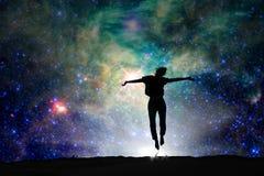 Silhouet van een vrouw die, sterrige nacht springen royalty-vrije stock afbeelding