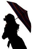 Silhouet van een vrouw die uit tong plakken Stock Foto's