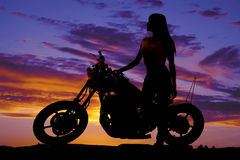 Silhouet van een vrouw die zich door een motorfiets bevinden die vooruit eruit zien royalty-vrije stock foto's