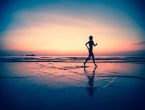 Silhouet van een vrouw jogger op het strand bij zonsondergang Stock Foto