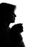 silhouet van een vrouw met een kat in haar wapens Stock Afbeeldingen