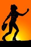 Silhouet van een vrouw met haar hoed het in hand omhoog bereiken Stock Foto
