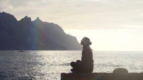 Silhouet van een vrouwenzitting op rotsen en het waarnemen van oceaangolven bij zonsondergang in Tenerife, Canarische Eilanden stock footage
