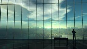 Silhouet van een zakenman tegen het reusachtige bureauvenster stock footage