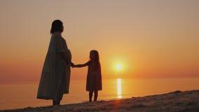 Silhouet van een zwangere vrouw met een dichtbij langs baby Tribune dichtbij het overzees bij zonsondergang Het wachten op de twe stock afbeelding