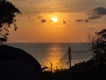 Silhouet van elektrodraden tegen de zon die in het overzees plaatsen stock foto
