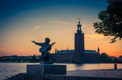 Silhouet van Evert Taube standbeeld en het Stadhuis van Stockholm, Zweden stock foto