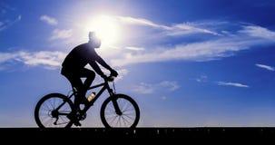 Silhouet van fietser het berijden Stock Foto's