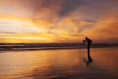 Silhouet van fotograaf op het strand stock afbeelding