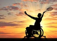 Silhouet van gehandicapte persoon in een rolstoel speeltennis stock foto