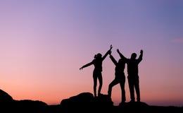 Silhouet van gelukfamilie met omhoog opgeheven wapens Mooie sk Royalty-vrije Stock Afbeelding