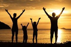 Silhouet van gelukkige familie die die op het strand bij de zonnen spelen Stock Foto