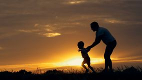 Silhouet van gelukkige familievader van moeder en twee zonen die in openlucht op gebied bij zonsondergang spelen stock video