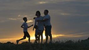 Silhouet van gelukkige familievader van moeder en twee zonen die in openlucht op gebied bij zonsondergang spelen stock footage