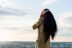 Silhouet van gelukkige glimlachende jonge zwarte Afrikaanse Amerikaanse vrouw die met lang haar aan muziek luisteren Vage citysca stock foto's