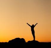 Silhouet van gelukkige jonge vrouw tegen mooie kleurrijke hemel stock afbeelding