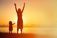 Silhouet van gelukkige moeder en weinig dochter bij royalty-vrije stock fotografie