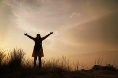 Silhouet van gelukkige vrouw die van aard, plezier van aard en vrijheid genieten stock afbeeldingen