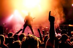 Silhouet van gitaarspeler in actie betreffende stadium royalty-vrije stock foto's