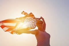 Silhouet van glimlachende vrouw in zonnebril met opgeheven handen met de vlag van de V.S. royalty-vrije stock foto's