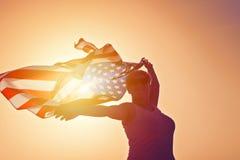 Silhouet van glimlachende vrouw in zonnebril met opgeheven handen met de vlag van de V.S. stock foto's