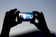 Silhouet van handen met een smartphone bij een groot muziekfestival Stock Foto