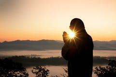 Silhouet van het christelijke mensenhand bidden, spiritualiteit en godsdienst, mens die aan god bidden stock foto